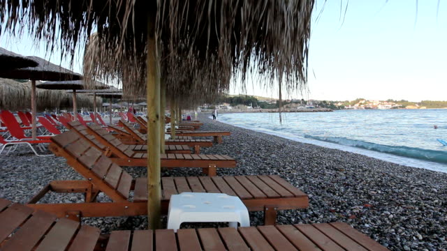 Wooden loungers with straw umbrellas for relaxing by the beach video