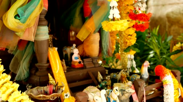 木製ミニチュア保護者精神の家。小さな仏教寺院神社、カラフルな花の花輪。サン ・ プラ ・ プムがもたらす幸運に建立します。伝統的な敬意アニミズム儀式、祈りの儀式 - サムイ島点の映像素材/bロール