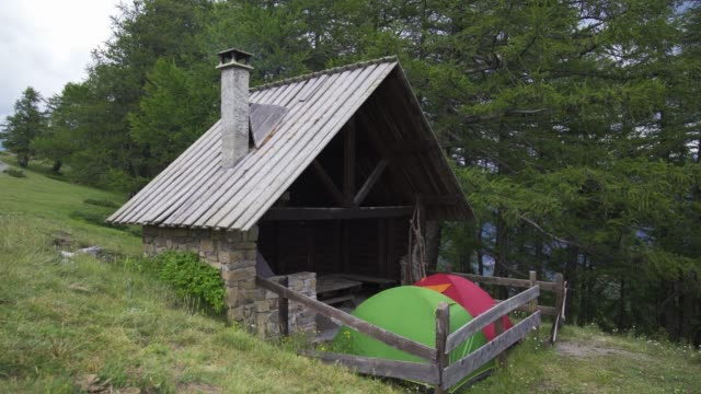 wooden mountain shelter with smoking chimney