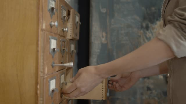 Wooden organizer for storing registration cards, female hands open and close