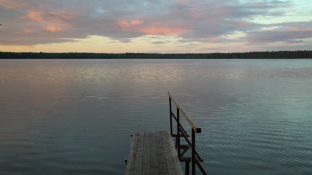 Wooden pier by the lake with burning sunrise sky and forest in the background. Colourful sunset sky by the water shore. Peaceful time camping in nature
