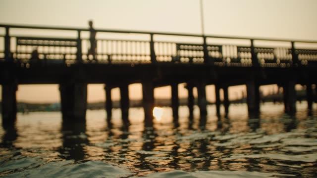 göl üzerinde gün batımı nda ahşap iskele - dalgakıran stok videoları ve detay görüntü çekimi