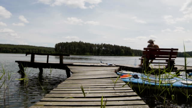 Wooden pier on a lake. Idyllic landscape. Man resting on a bench video