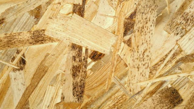 木製プレート osb 押された木製のおがくずから回転テキストのクローズ アップの背景 - おがくず点の映像素材/bロール