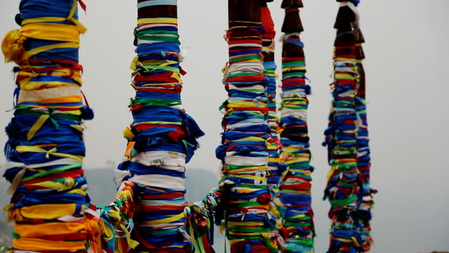 Wooden shaman totems with ribbons near holy cape Burkhan on island Olkhon island on lake Baikal in Russia.  tourists visit the island as amulets and promises given to this place