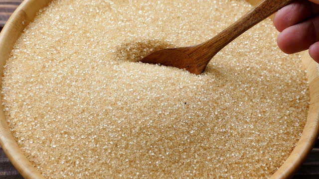 wooden spoon pouring white sugar in bowl - сахарный тростник стоковые видео и кадры b-roll