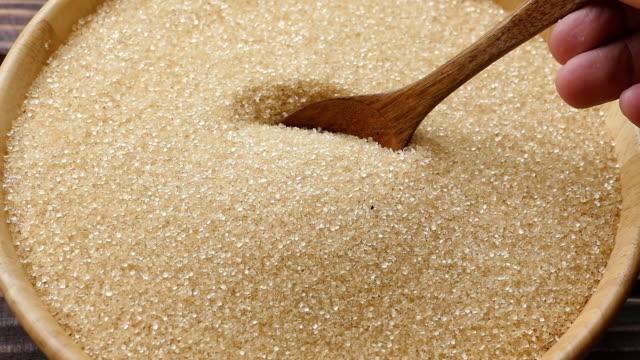 wooden spoon pouring white sugar in bowl - canna da zucchero video stock e b–roll
