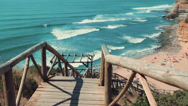 Wooden stairway to the epic beach in Portugal. Waves break on the shore with steep cliffs in the background.