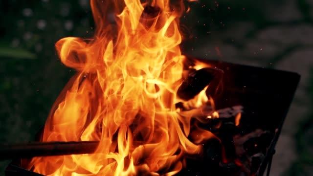 vídeos de stock e filmes b-roll de wooden stick is mixing logs in bright fire. - inflamável