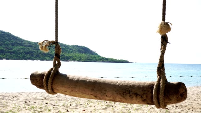 Wooden swing on white clear beach at Samsarn Island Sattahip, Chon Buri Thailand. Tropical beautiful view holiday relaxing of sea nature of blue clean ocean with summer sky clear view landscape.