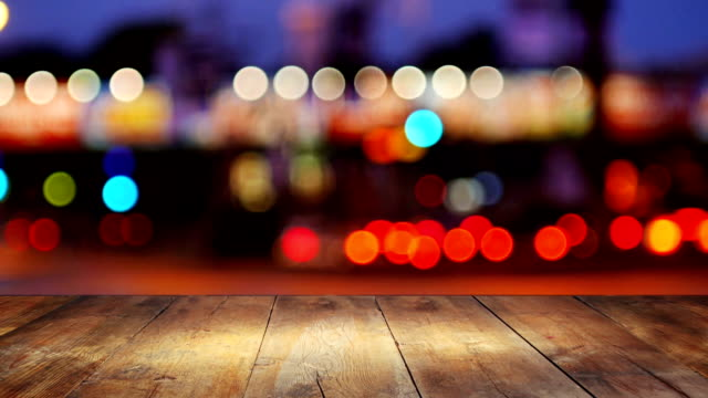 Wooden table in front of abstract background of city lights video