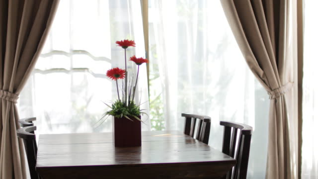 vídeos de stock e filmes b-roll de wooden table with flower vase blur curtain window with green garden , dolly shot right to left - living room background