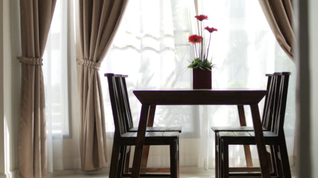 vídeos de stock e filmes b-roll de wooden table with flower vase blur curtain window with green garden - living room background