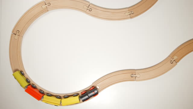 TOP VIEW: Wooden toy train move on curve wooden railways (stop motion) - Vidéo