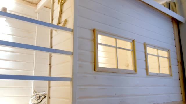 Wooden white house in kids room with windows and bed inside. video