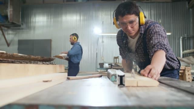 holzarbeiter schneidet sperrholz in werkstatt - kreissäge stock-videos und b-roll-filmmaterial