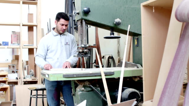 woodworker sawing wood with a band saw - carpenter in carpentery - dolly video