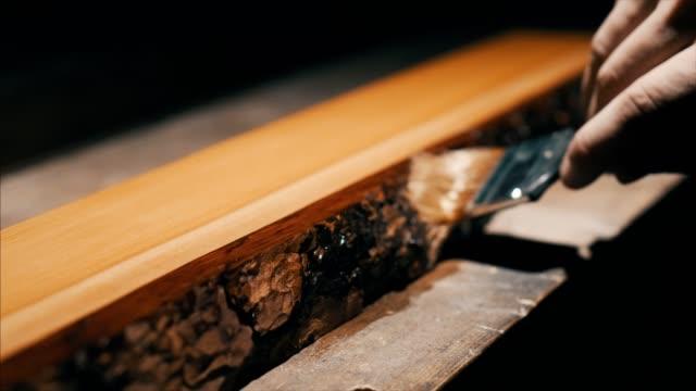 holzarbeiter zum malen über rinde des ulmenholzes, um es vor der umwelt zu schützen - bauholz brett stock-videos und b-roll-filmmaterial