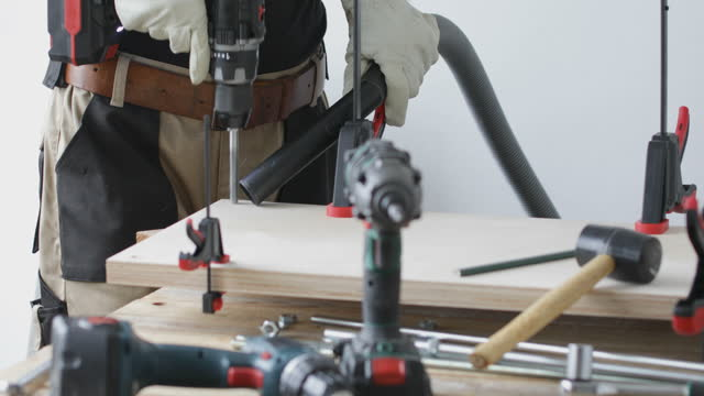 Woodworking craftsman drilling hole on plywood plates video