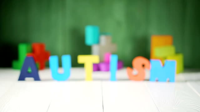 Word AUTISM with a pieces of puzzle on white wooden background. Word AUTISM with a pieces of puzzle on white wooden background. Autism Spectrum Disorder (ASD) concept. autism stock videos & royalty-free footage