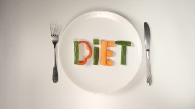 TOP VIEW: Word DIET from a vegetables on a white dish (stop motion) video
