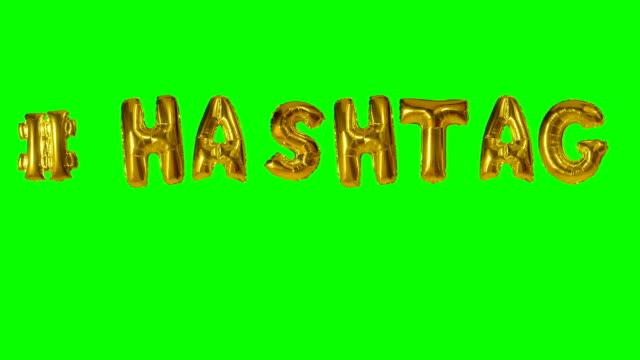word hashtag från helium guld ballong bokstäver flytande på grön skärm - stavning bildbanksvideor och videomaterial från bakom kulisserna