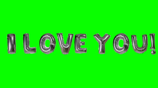 Word I love you from helium silver balloon letters floating on green screen