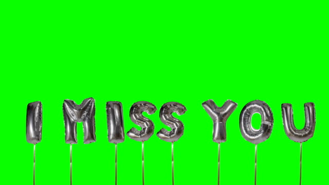 Word I miss you from helium silver balloon letters floating on green screen