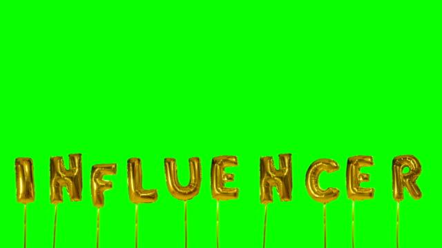 グリーンスクリーンに浮かぶヘリウム黄金の風船文字からの単語インフルエンサ - アイコン プレゼント点の映像素材/bロール