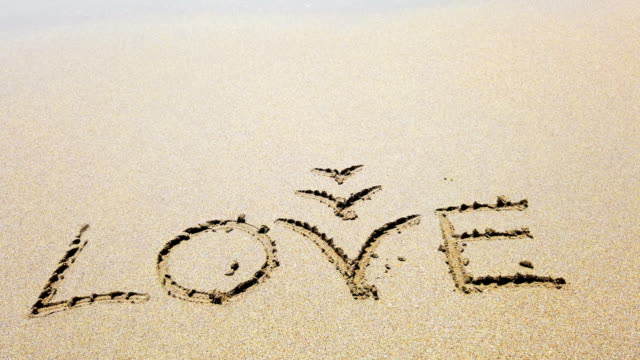 word love on the sand that wiped off by sea wave - divorzio video stock e b–roll