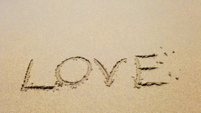 word love on the sand - parola video stock e b–roll