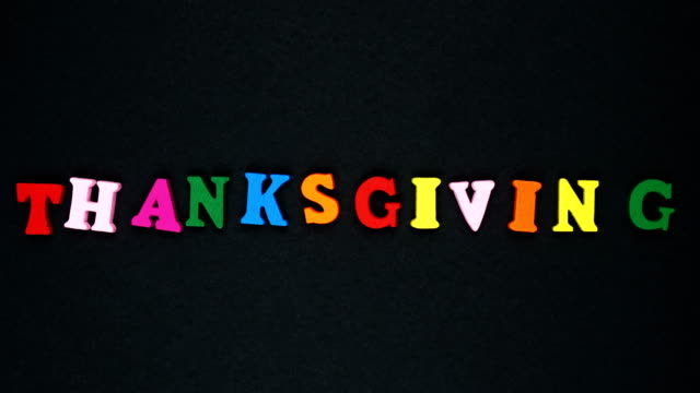 "word ""thanksgiving"" formed of wooden multicolored letters. colorful words loop. - parola video stock e b–roll"