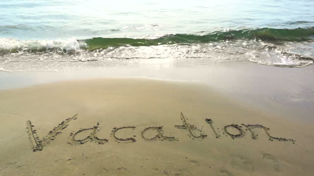 Word Vacation handwritten on sandy beach. Relax on weekend concept.
