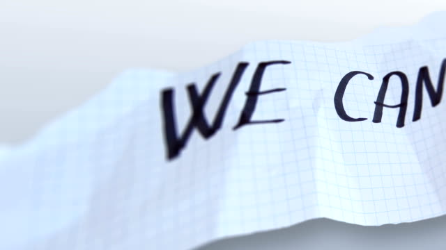 word' we can '  on torned paper  on gradient background video