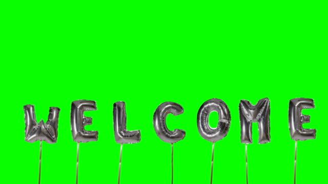 gruß von helium silbernen ballonbuchstaben, die auf grüner leinwand schweben - welcome stock-videos und b-roll-filmmaterial