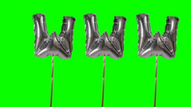 Word www web internet from helium silver balloon letters floating on green screen