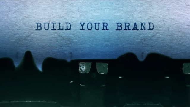 BUILD YOUR BRAND words Typing on a sheet of paper with an old vintage typewriter. BUILD YOUR BRAND Word closeup Being Typing and Centered on a Sheet of paper on old vintage Typewriter mechanical 4k Footage Background Animation. advertisement stock videos & royalty-free footage