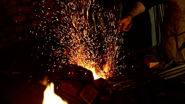 Work : Blacksmith working, flame and sparks. (CINE CRANE) Blacksmith works are blowing the horn, up to red glowing metal, flames and sparks. anvil stock videos & royalty-free footage