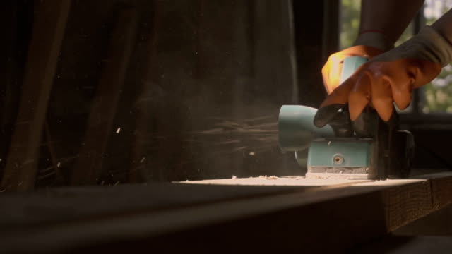 Work carpenter in the workshop. Electric Planer. Treatment of wooden planks electric tool in slow motion video