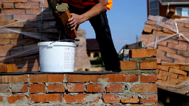 work lays bricks on a construction site on open air - mattone video stock e b–roll