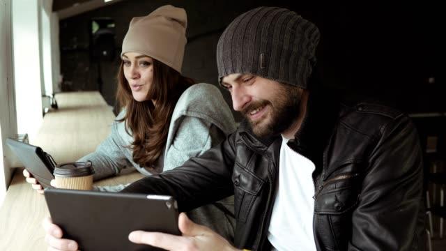 arbeitstreffen in kreativbüro. junger mann und frau mit einem tablet, um video zu sehen. schuss in 4k - reisebüro stock-videos und b-roll-filmmaterial