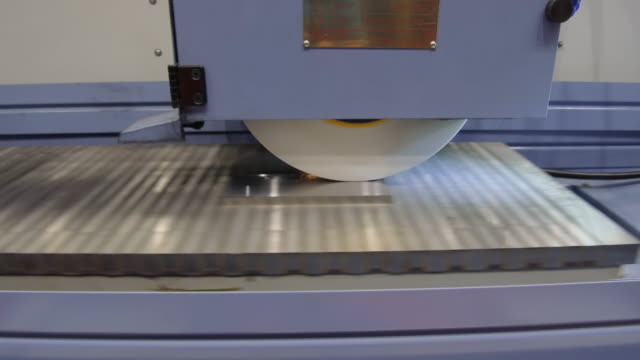 work of an industrial surface grinding machine. grinding of a flat metal part. - rettificatrice video stock e b–roll
