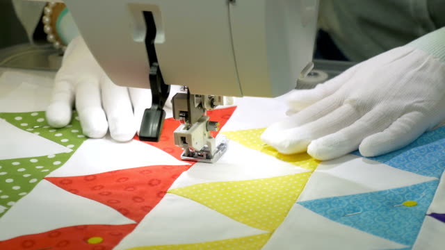 vídeos de stock e filmes b-roll de work on a sewing machine. a woman in white gloves scribbles on the fabric. - edredão