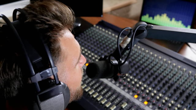 work on radio, man with headphones on head speaks into microphone video