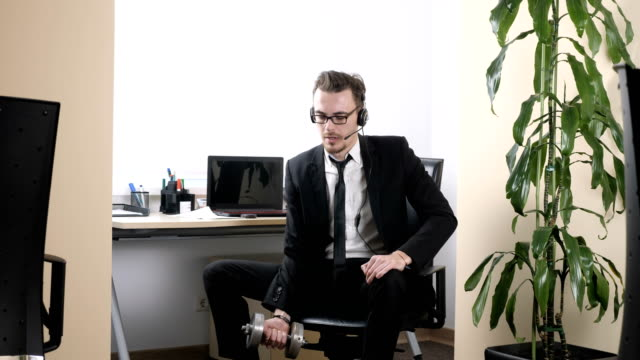 Work out in the office, man in a suit does an exercise for the biceps while sitting in the office and speaking on the headset. 60 fps video