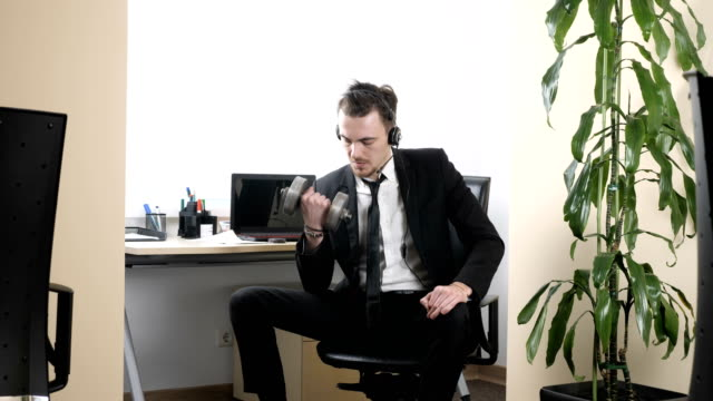 Work out in the office, man in a suit does an exercise for the biceps while sitting in the office and speaking on the headset 60 fps video