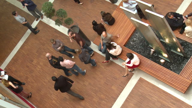 HD: Work Place HD1080p: High angle view of the lobby of an office building where workers are passing by and gathering to have a conversation. lobby stock videos & royalty-free footage