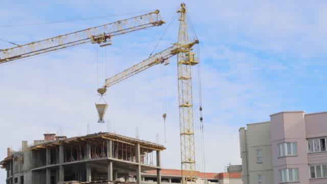 工事現場の作業棟クレーン。クレーンは建設中の建物の上から地面にコンクリートのビンを移動します。 - クラシファイド広告点の映像素材/bロール