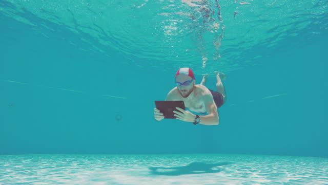 vídeos de stock e filmes b-roll de viciado em trabalho homem usando comprimido debaixo de água numa piscina - crianças todas diferentes