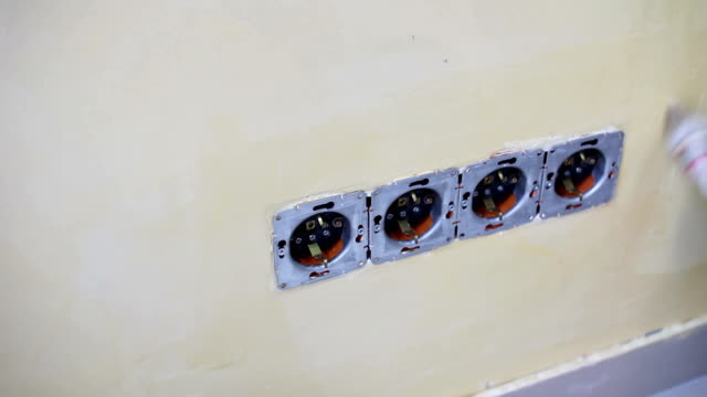 Worker adhesive wallpapers. He put glue near the sockets on the wall using a brush video